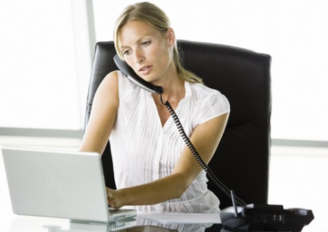 A woman on the telephone while working at a laptop